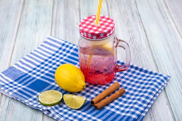 Vista dall'alto di limoni freschi sulla tovaglia a quadretti blu con bastoncini di cannella con succo sul barattolo di vetro su legno grigio