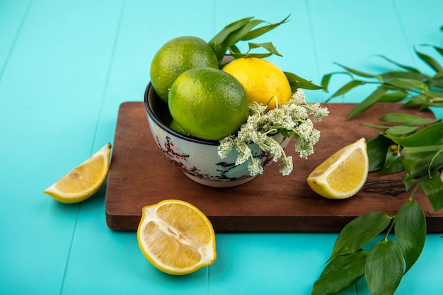 Top view of fresh lemons on bowl on wood kitchen board with leaves on blue