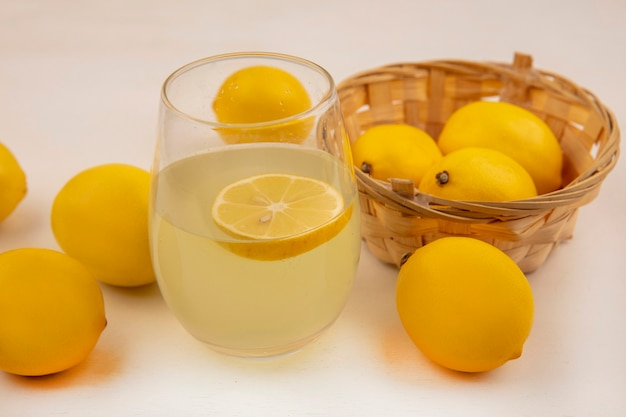 Top view of fresh lemons on a bucket with fresh lemon juice in a glass on a white wall