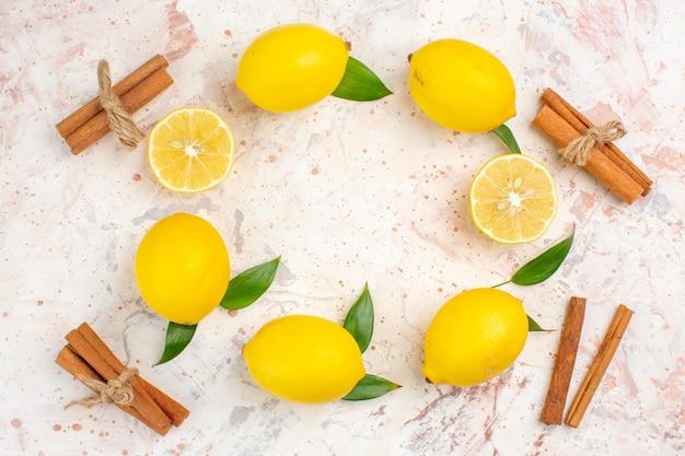 Vista dall'alto di limoni freschi a forma di cerchio, limoni tagliati a bastoncini di cannella sulla brillante superficie isolata