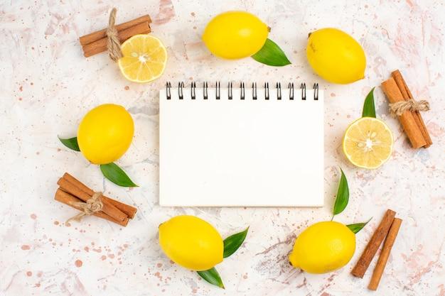 Limoni freschi di vista superiore in un taccuino dei bastoni di cannella dei limoni tagliati di forma del cerchio sulla superficie isolata luminosa