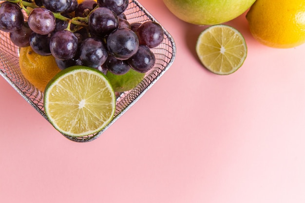 Top view of fresh lemons citruses inside fryer with apple and grapes on light pink surface
