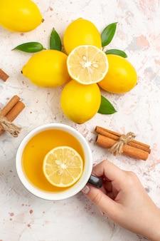 上面図新鮮なレモンカットレモンシナモンは、明るい孤立した表面に女性の手でレモンティーのカップを貼り付けます