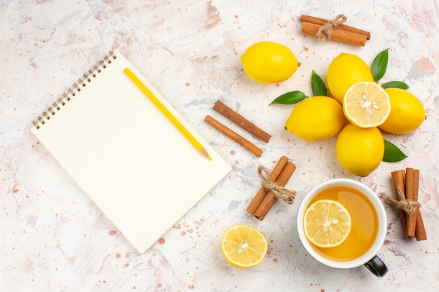 상위 뷰 신선한 레몬 잘라 레몬 계피는 밝은 고립 된 표면에 레몬 차 노트북의 컵을 스틱