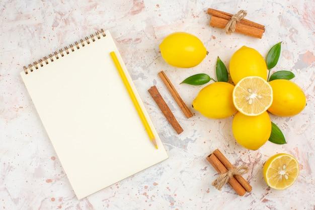 Vista dall'alto limoni freschi tagliati limone bastoncini di cannella notebook e matita gialla su brillante superficie isolata