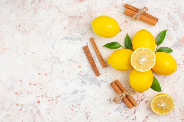 上面図新鮮なレモンは、明るい孤立した表面の空きスペースにレモンシナモンスティックをカットしました