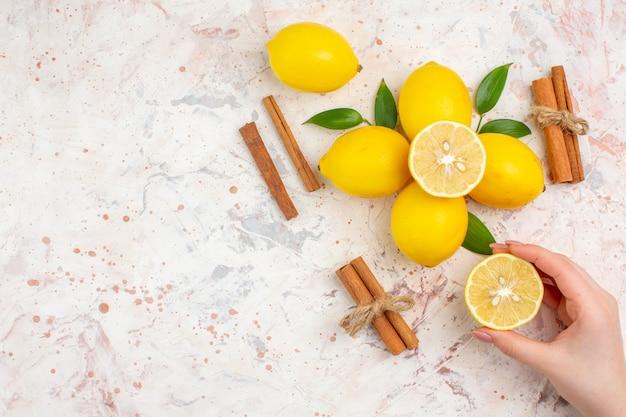 上面図新鮮なレモンは、明るい孤立した表面の自由空間に女性の手のシナモンスティックでレモンをカットしました