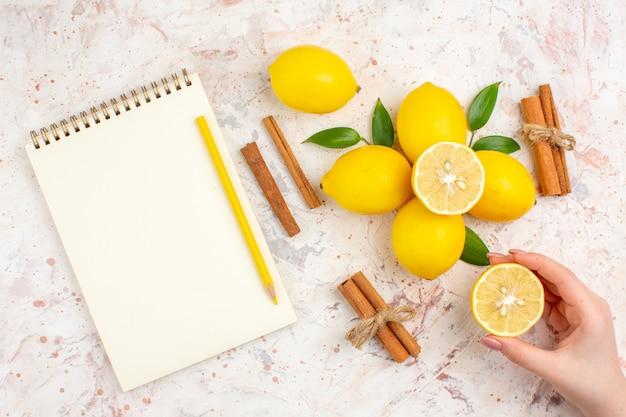 上面図新鮮なレモンは女性の手でレモンをカットシナモンは明るい孤立した表面に女性の手で黄色の鉛筆をスティックします