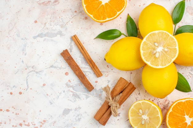 Top view fresh lemons cut orange cinnamon on bright isolated surface free place