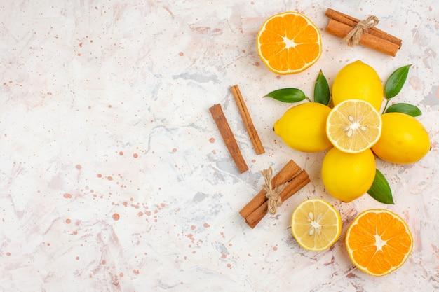 Top view fresh lemons cut orange cinnamon sticks on bright isolated surface free place