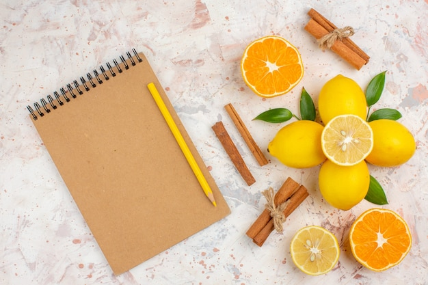 Top view fresh lemons cut orange cinnamon sticks cut orange in female hand notebook yellow pencil on bright isolated surface