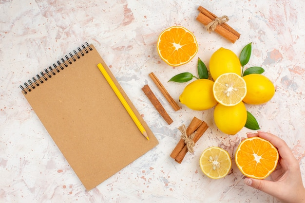 上面図新鮮なレモンカットオレンジシナモンスティック明るい孤立した表面上の女性の手ノート鉛筆でオレンジをカット