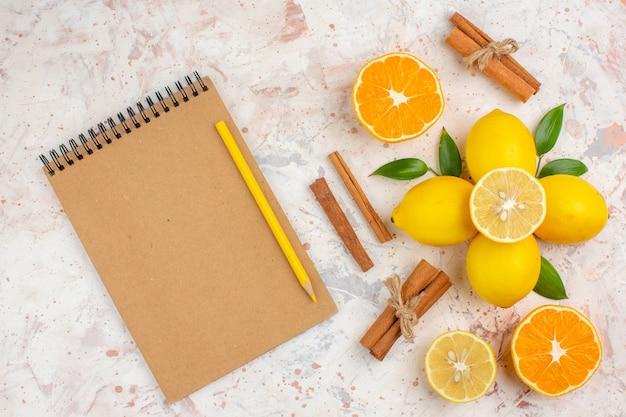 Вид сверху свежие лимоны, разрезанные апельсиновые палочки корицы, разрезанные апельсины в женской руке, блокнот, желтый карандаш на яркой изолированной поверхности
