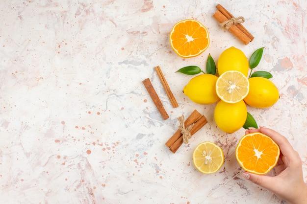 上面図新鮮なレモンカットオレンジシナモンスティック明るい孤立した表面の空きスペースに女性の手でオレンジをカット