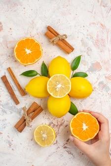 上面図新鮮なレモンカットオレンジシナモンスティック明るい孤立した表面に女性の手でオレンジをカット