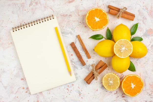 Вид сверху свежих лимонов, нарезанных оранжевыми палочками корицы, желтым карандашом на блокноте на яркой изолированной поверхности
