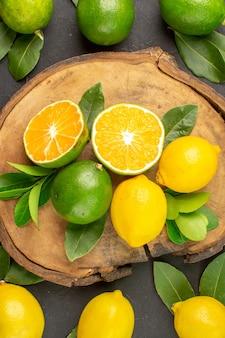 Limoni freschi di vista superiore sugli agrumi della frutta acida della calce scura della tavola