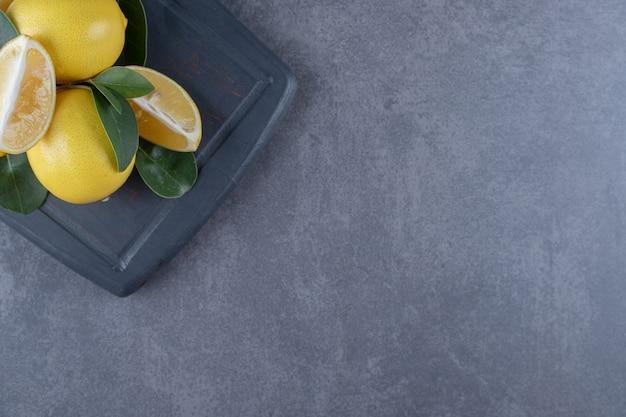 Top view of fresh lemons on grey wooden board.