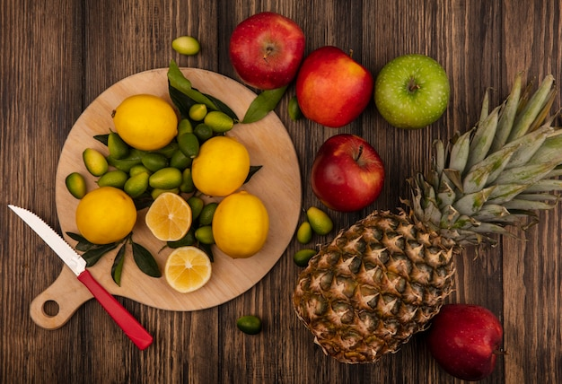 Top view of fresh lemons isolated on a wooden kitchen board with apples and pineapples isolated on a wooden surface