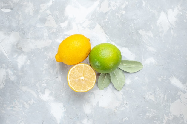 Вид сверху свежие лимоны сочные и кислые на белом столе тропические экзотические фрукты цитрусовые