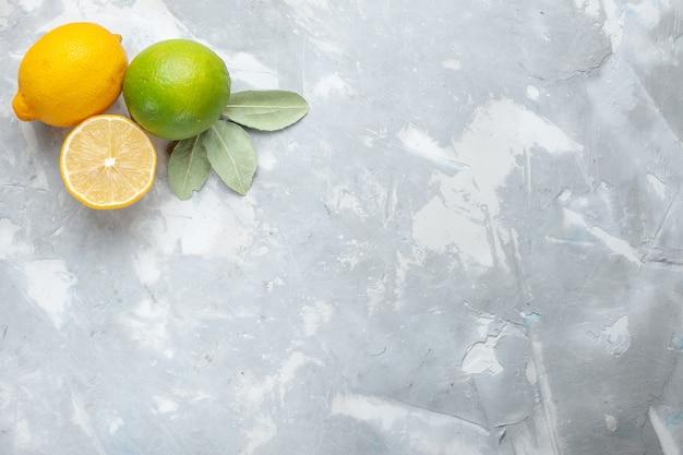 Вид сверху свежие лимоны, сочные и кислые на белом столе, тропические экзотические фрукты, цитрусовые