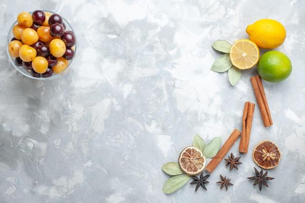 Вид сверху свежие лимоны, сочные и кислые с корицей и вишней на белом столе, тропические экзотические фрукты, цитрусовые