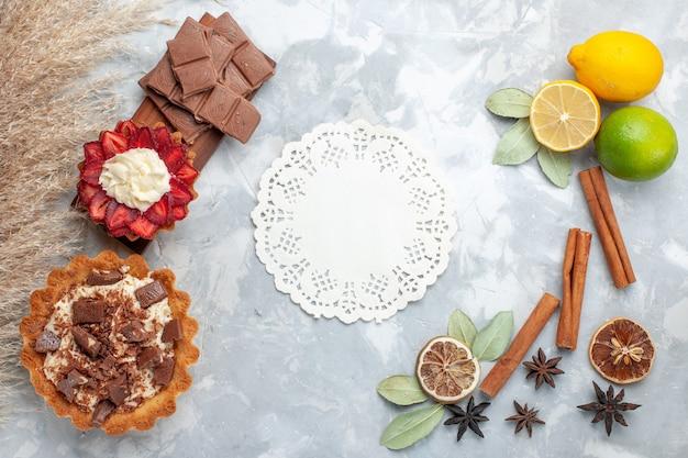 Вид сверху свежие лимоны сочные и кислые с корицей, шоколадом и пирожными на белом столе тропические экзотические фрукты цитрусовые