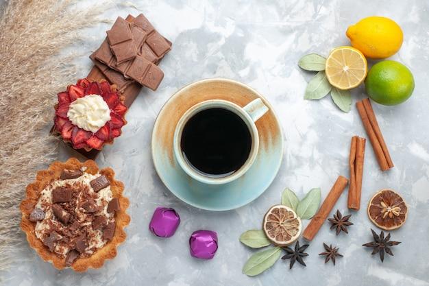Вид сверху свежие лимоны, сочные и кислые, с корицей, шоколадным чаем и пирожными на белом столе, тропические экзотические фрукты, цитрусовые