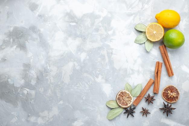 トップビュー新鮮なレモンジューシーで酸っぱいシナモンと白い机の熱帯のエキゾチックなフルーツ柑橘類
