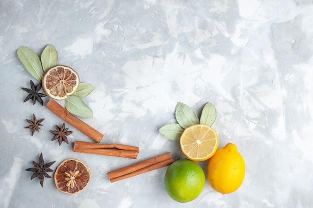 トップビュー新鮮なレモンジューシーで酸っぱい白い机の上にシナモントロピカルエキゾチックフルーツ柑橘類