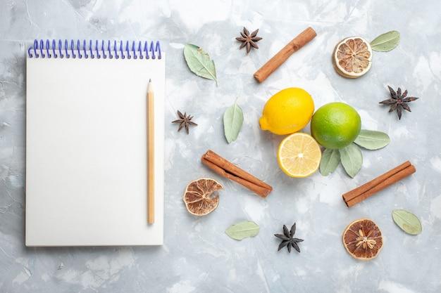 Limoni freschi di vista superiore succosi e aspri con cannella e blocco note sugli agrumi tropicali della frutta esotica dello scrittorio bianco