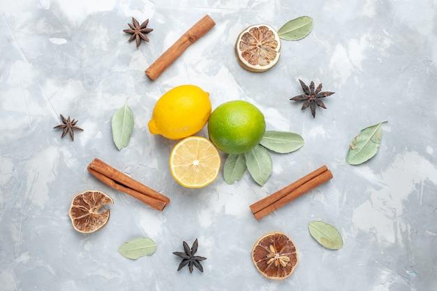 Limoni freschi di vista superiore succosi e aspri con cannella sugli agrumi tropicali della frutta esotica dello scrittorio bianco