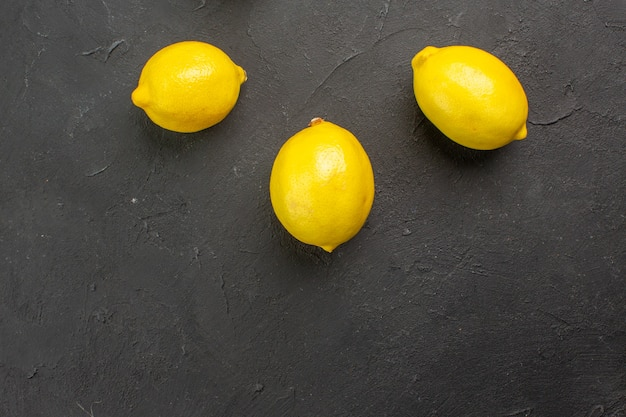 Top view fresh lemons lined on dark table citrus yellow fruit lime