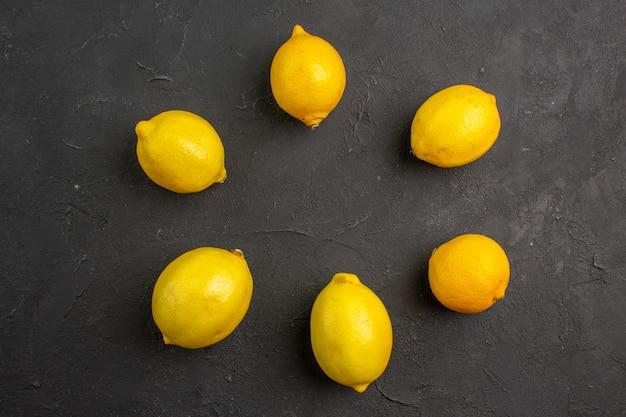 Вид сверху свежие лимоны, выложенные на темном столе, цитрусовые, желтые фрукты, экзотические