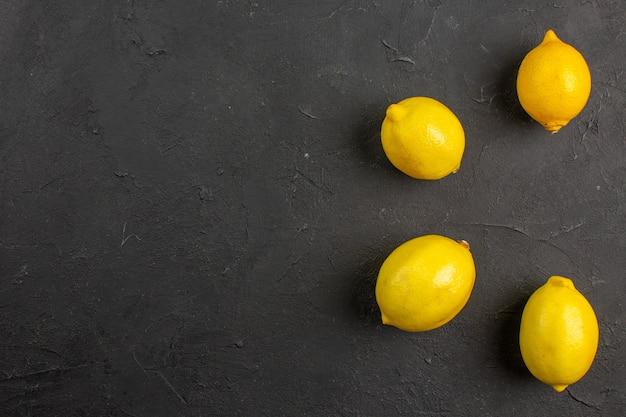 Вид сверху свежие лимоны, выложенные на темном столе, цитрусовые, желтые фрукты, свободное пространство для текста