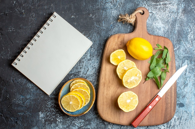 Top view of fresh lemons and mint knife on a wooden cutting board next to notebook on dark background