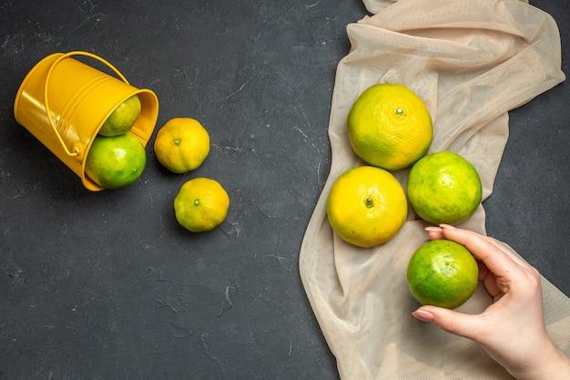 어두운 표면에 여성 손에 양동이 레몬에서 흩어져 베이지 색 tule 목도리 레몬에 상위 뷰 신선한 레몬