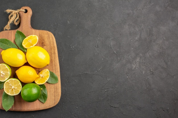 Top view fresh lemons sour fruits on dark-grey table citrus lime fruits