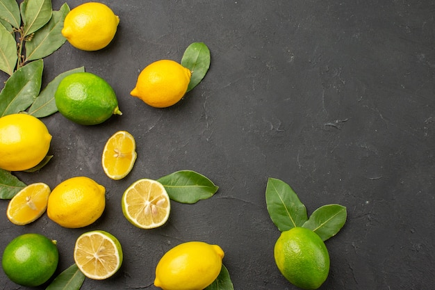 Top view fresh lemons sour fruits on a dark table citrus lime fruit