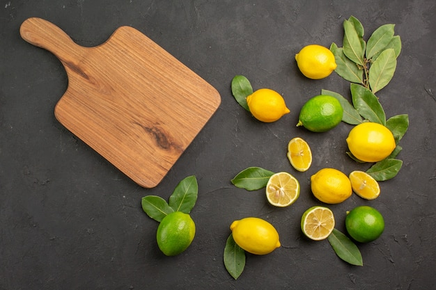 Top view fresh lemons sour fruits on dark table citrus lime fruits