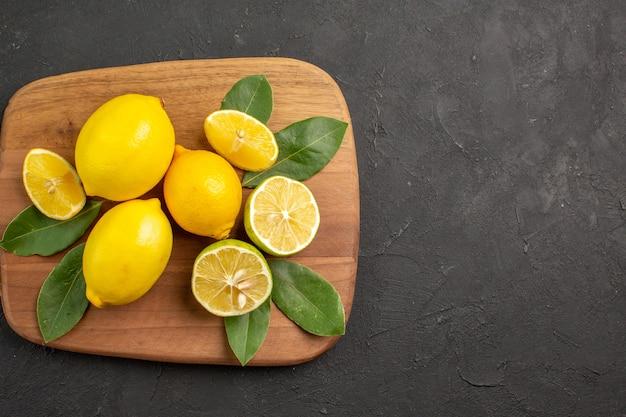 トップビューフレッシュレモンサワーフルーツ、ダークグレーのテーブルシトラスフルーツライム