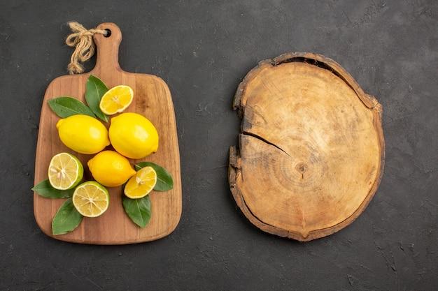 トップビューフレッシュレモンサワーフルーツ、ダークグレーのテーブルシトラスライムフルーツ