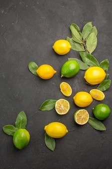 トップビューダークテーブルの新鮮なレモンサワーフルーツ柑橘系ライムフルーツ