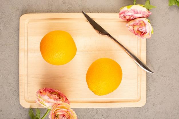 Una vista dall'alto limoni freschi aspri maturi agrumi morbidi succosi insieme a rose secche tropicale vitamina gialla sulla scrivania crema