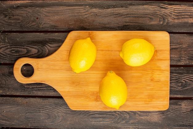Una vista dall'alto limoni freschi maturi aspro agrume dolce succosa vitamina tropicale giallo sulla scrivania rustica marrone