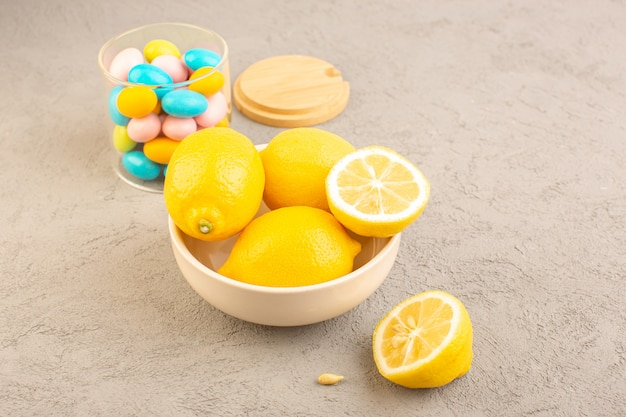 A top view fresh lemons sour ripe whole mellow with colorful sweet candies citrus tropical vitamine yellow on the cream desk