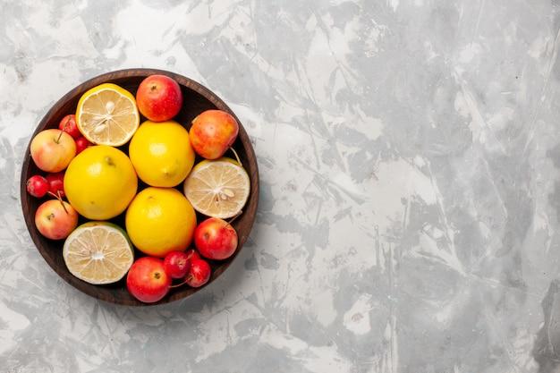 Vista dall'alto di limoni freschi interi e affettati su uno spazio bianco