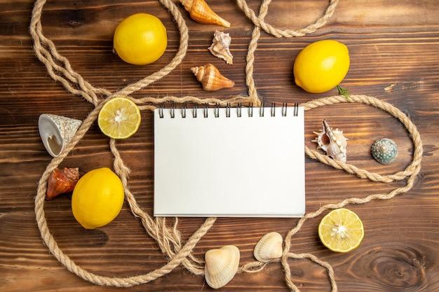 茶色の机の上にロープで新鮮なレモンの上面図