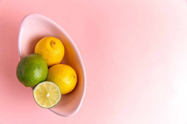 Vista dall'alto di limoni freschi con calce a fette all'interno della piastra sulla superficie rosa