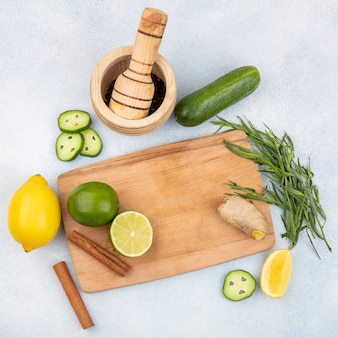 Vista dall'alto di limoni freschi sulla tavola di cucina in legno con bastoncini di cannella e zenzero con verdi di dragoncello su bianco